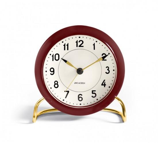 Stations uret i Bordeaux rød med guld farvet fod fra Arne Jacobsen